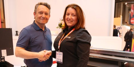 Rob Harrison of the Handsome Prints Company shakes hands on the deal with Sarah Fenna on the CMYUK stand at Sign & Digital UK