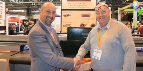 Steve Tilbury (left) and Hallmark Equipment Service Ltd's Gary Hall shake on the deal at QPS's Sign UK stand
