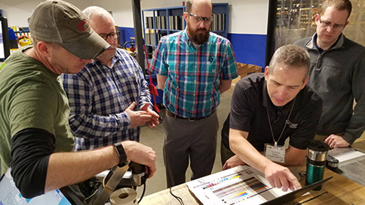 Hub Labels and Nazdar consultants review test prints and color curve data.