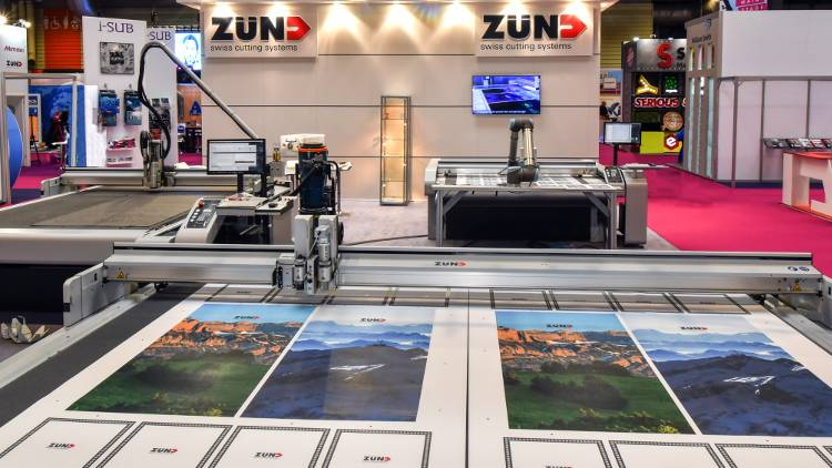 Featuring the clean red, black and white branding of Zünd, stand K30 attracted attention for its next-generation cutting systems, in particular a Zünd S3 L1200 fitted with a robotic arm.
